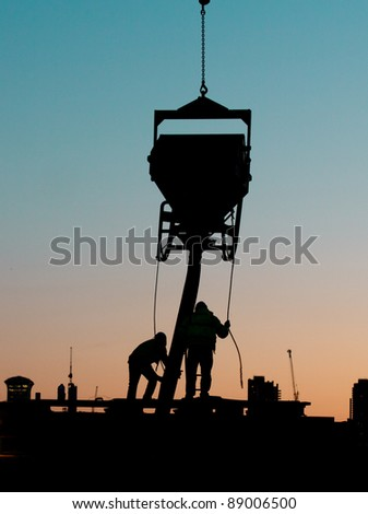 Silhouette of builders doing construction work at sunset - stock photo