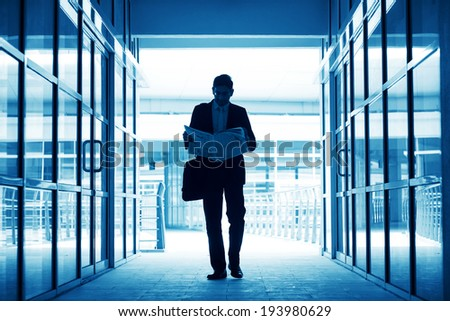 Silhouette of business man residing newspaper and walking thru modern office building, in blue tone. - stock photo