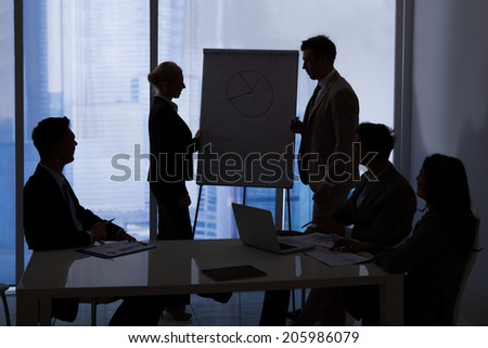 Silhouette of business people having a discussion in conference room - stock photo