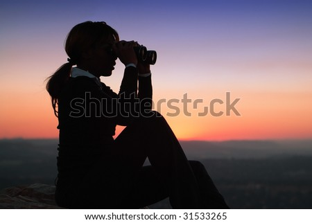 Silhouette of Business Woman with Binoculars Sitting on a Hilltop - stock photo