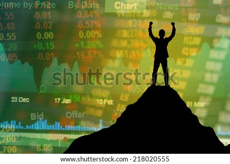 Silhouette of businessman hold up hands on the peak of mountain and stock exchange board background,success concept - stock photo