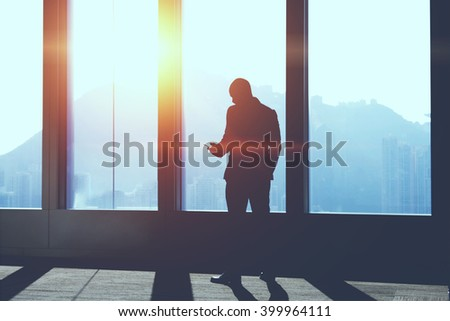 Silhouette of businessman is searching information on web page via mobile phone, while is standing in office interior against skyscraper window background with copy space for your advertising content - stock photo