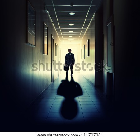 Silhouette of businessman standing in office building corridor against light