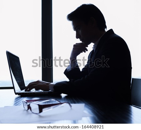 Silhouette of businessman using computer