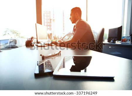 Silhouette of businessman using laptop in office - stock photo