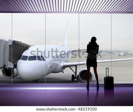 silhouette of businesswoman which expects flight aboard the plane at airport - stock photo