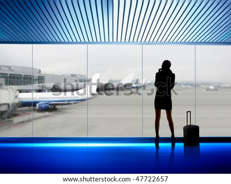 silhouette of businesswoman which expects flight aboard the plane in airport - stock photo