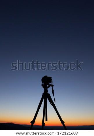 silhouette of camera on tripod  - stock photo
