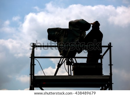 Silhouette of cameraman and video equipment on a tripod at the workplace outdoors - stock photo
