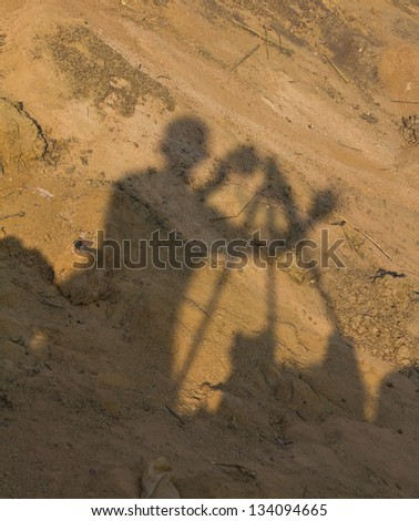 Silhouette of cameraman photographed on the ground. - stock photo