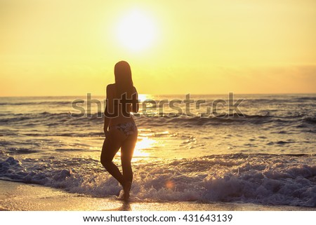 Silhouette of carefree woman on the beach at sunrise