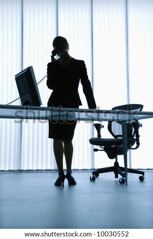 Silhouette of Caucasian businesswoman standing at computer desk on telephone. - stock photo