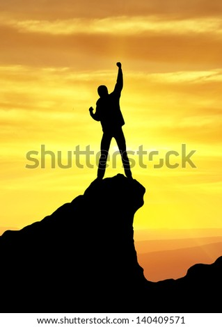 Silhouette of champion on the rock. Sport and active life - stock photo