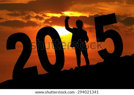Silhouette of cheerful entrepreneur expressing success and forming number 2015 at sunset time - stock photo