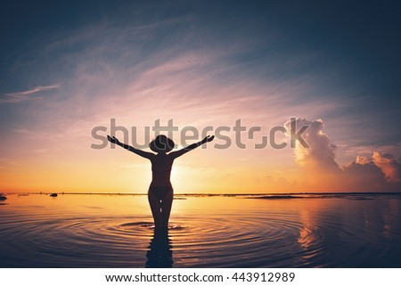 Silhouette of cheerful woman in hat meeting sunrise in ocean (intentional vintage color)