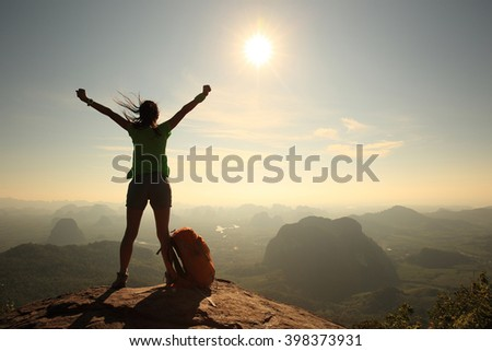 silhouette of cheering woman hiker open arms at mountain peak - stock photo