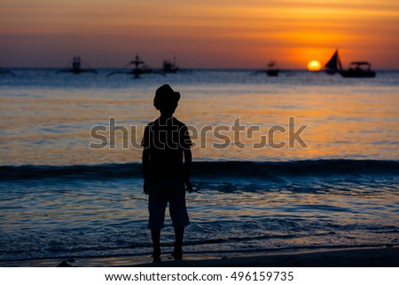 Silhouette of child in hat on the beach on the dawn time