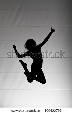 silhouette of child jumping on trampoline - stock photo