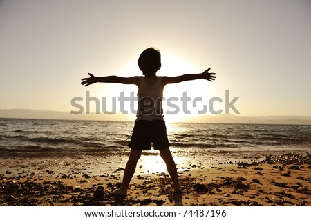 Silhouette of child on the beach, holding his hands up, hugging the sun - stock photo