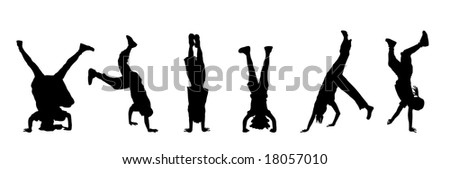 silhouette of children doing headstands and handstands - stock photo