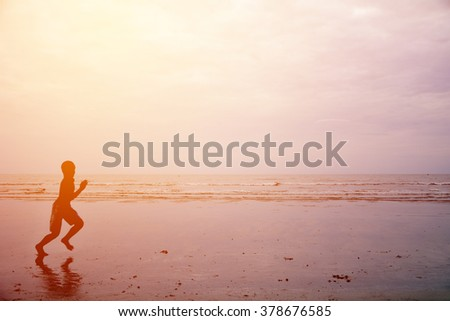 Silhouette of children playing at the beach.