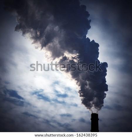 silhouette of chimney-stalk with smoke - stock photo