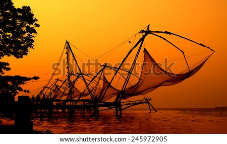 Silhouette of Chinese fishing(unique fishing technology in the world) nets constructed at  port, taken at dusk against a romantic background in the Arabian sea,Fort Kochi(Cochin),Kerala,India - stock photo