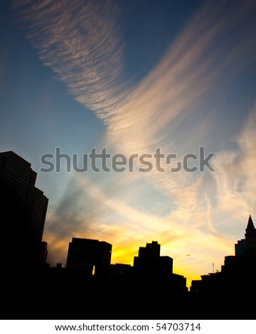 Silhouette of city skyline during sunset with an impressive sky - stock photo