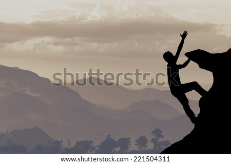 Silhouette of climber, layer mountain background  - stock photo