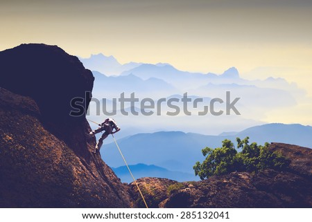 Silhouette of climber on a cliff against misty mountain valley - stock photo