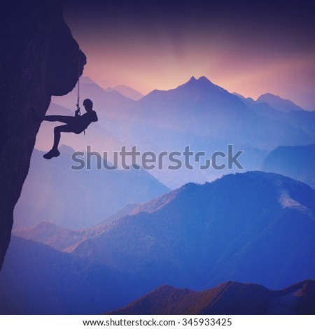 Silhouette of climber on a cliff against misty mountain valley. Vintage colors - stock photo
