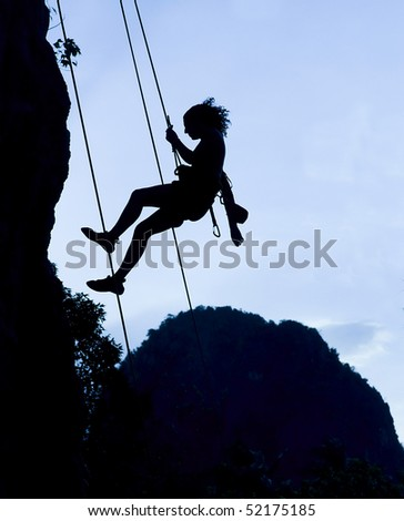 Silhouette of climbing woman in Railey, Thailand - stock photo