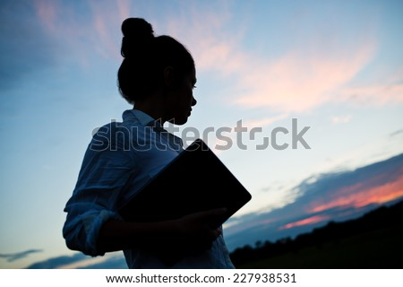 Silhouette of confident business woman holding tablet outside in front of blue sky. Dramatic photo with atmospheric sunset light. Woman looking to the future. - stock photo
