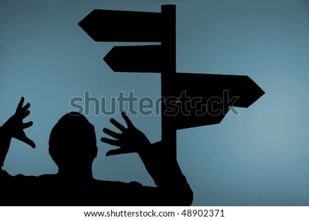 Silhouette of confused man with hands in air under multiple directional signpost, light blue background. - stock photo