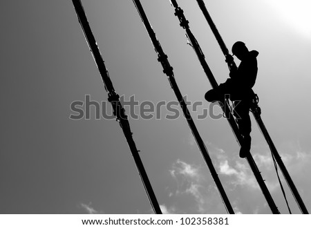 Silhouette of construction climber on suspension bridge - stock photo