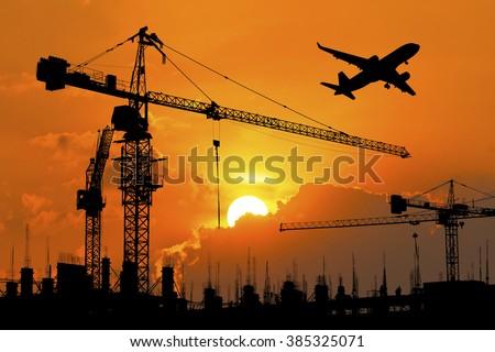 silhouette of construction site crane - stock photo