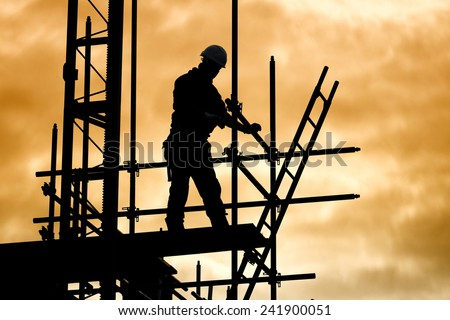 silhouette of construction worker against sky on scaffolding with ladder on building site at sunset - stock photo