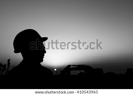 Silhouette of construction worker at construction site in oilfield - Blur background with heavy lifting equipment - Sunset.- Black and white  - stock photo