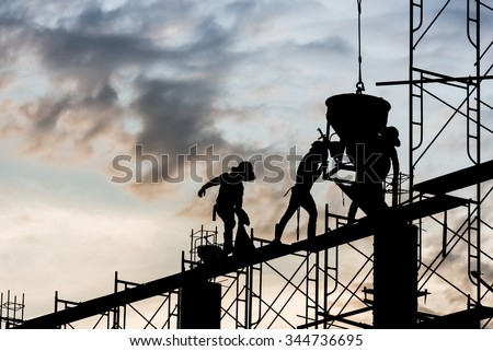 Silhouette of construction worker. Casting concrete work on scaffolding in the construction site. - stock photo