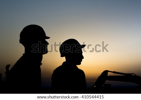 Silhouette of construction workers at construction site in oilfield - Blur background with heavy lifting equipment - Sunset.    - stock photo