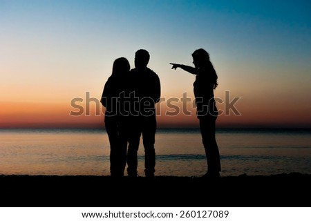 Silhouette of couple and a  friend in the morning at the beach and one of them pointing towards  sunrise . Support, together, winning, helping, freedom concept. - stock photo