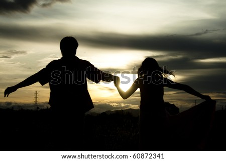 Silhouette of couple at sunset - stock photo
