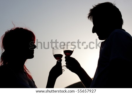 Silhouette of couple clinking glasses of wine - stock photo