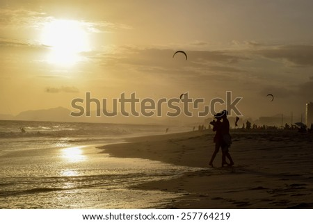 Silhouette of couple dancing a beach at stunning sunset - stock photo