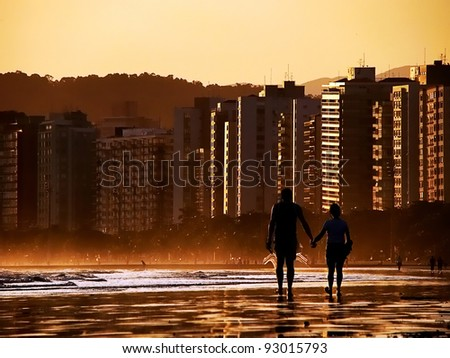 silhouette of couple holding hands walking on the beach