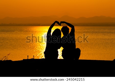 Silhouette of couple in love,Love sensuality and valentine day concept man and woman make heart sign  love at lake side  - stock photo