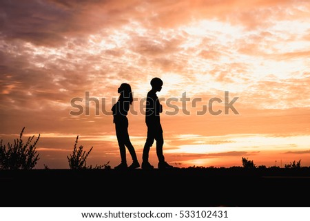 Silhouette of  couple in love ,man and women are quarrel in nature  in sunset time.