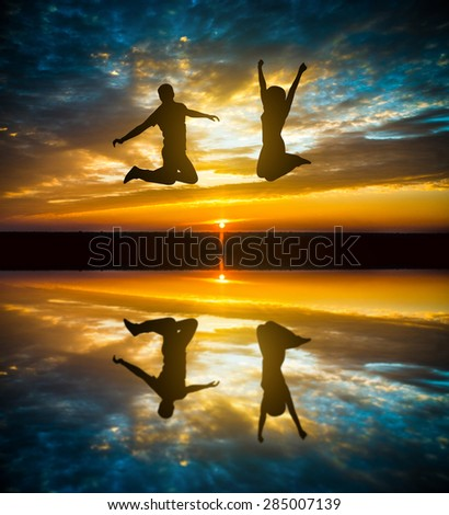 silhouette of couple  jumping in sunset - stock photo