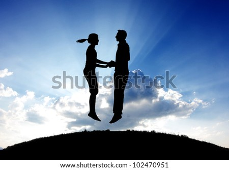 silhouette of couple jumping on top of hill - stock photo