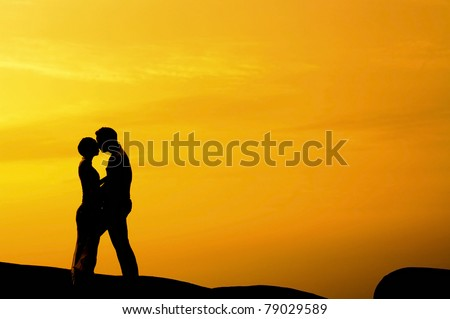 Silhouette of couple kissing in sunset